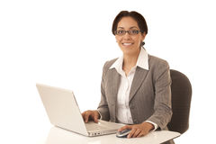 Hispanic business woman. Sitting at desk working on a laptop computer isolated on white Stock Photos