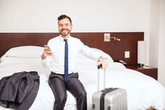 Hispanic businessman arriving at a hotel room. Portrait of a good looking young Hispanic businessman using a smartphone after just arriving to his hotel room Stock Photos
