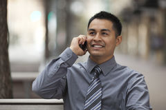 Hispanic Businessman - Chatting on cell phone. Stock photo of a Hispanic businessman sitting on a city bench and chatting on a cell phone with a happy expression stock photo