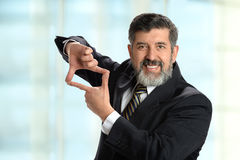 Hispanic Businessman Creating Frame with Hands Royalty Free Stock Photography