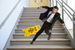 Hispanic Businessman Falling on stairs. Mature Hispanic businessman falling down the stairs Stock Photo