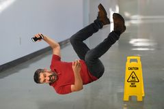 Man Falling on Floor. Hispanic businessman falling on wet floor inside building stock photography