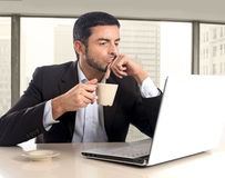 Hispanic businessman holding cup of coffee sitting at business district office desk working Stock Photos