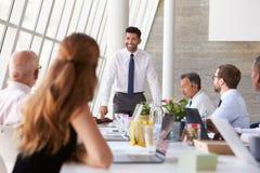 Hispanic Businessman Leading Meeting At Boardroom Table Stock Image