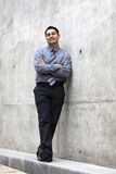 Hispanic Businessman - Leaning On Concrete Wall Royalty Free Stock Image