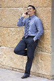 Hispanic Businessman - Leaning on stone wall Stock Photo