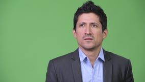 Hispanic businessman looking bored while thinking