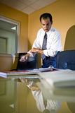 Hispanic businessman in office rolling up sleeves Stock Photography