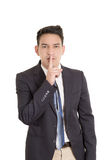 Hispanic businessman putting fingers on lips, shh Stock Images