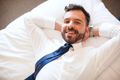 Hispanic businessman relaxing on a bed Royalty Free Stock Image
