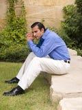 Hispanic businessman on rock Royalty Free Stock Photo