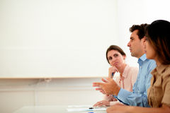 Hispanic businessman speaking during a conference. Portrait of hispanic businessman on blue shirt speaking during a conference while sitting between two lady on Stock Photo