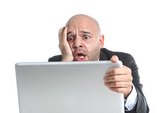 Hispanic businessman in stress at laptop holding monitor looking desperate Royalty Free Stock Photography