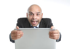 Hispanic businessman in stress at laptop holding monitor screaming desperate. Excited desperate businessman in stress at computer laptop holding monitor watching Stock Image