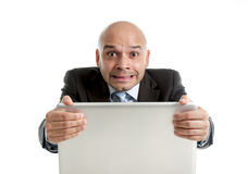 Hispanic businessman in stress at laptop holding monitor screaming desperate Stock Photos