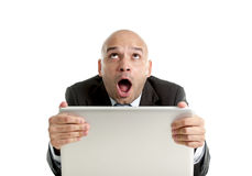 Hispanic businessman in stress at laptop holding monitor screaming desperate Royalty Free Stock Photography