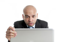 Hispanic businessman in stress at laptop holding monitor screaming desperate Stock Image