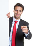 Hispanic businessman with suit and white board pointing at camera Royalty Free Stock Image