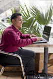 Hispanic Businessman - Telecommuting from Cafe Stock Photo
