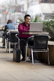 Hispanic Businessman - Telecommuting Internet Cafe. Stock photo of a well dressed Hispanic businessman looking down at a laptop while telecommuting from an royalty free stock image