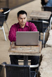 Hispanic Businessman - Telecommuting Internet Cafe. Stock photo of a well dressed Hispanic businessman looking down at a laptop while telecommuting from an royalty free stock photos