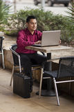 Hispanic Businessman - Telecommuting Internet Cafe. Stock photo of a well dressed Hispanic businessman looking down at a laptop while telecommuting from an royalty free stock images