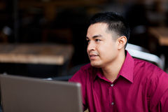 Hispanic Businessman - Telecommuting Internet Cafe. Stock photo of a well dressed Hispanic businessman working with a laptop while telecommuting from an internet royalty free stock photo