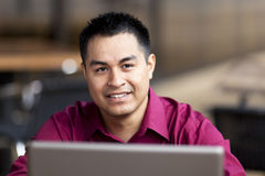 Hispanic Businessman - Telecommuting Internet Cafe. Stock photo of a well dressed Hispanic businessman looking up from a laptop while telecommuting from an stock photos