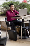 Hispanic Businessman - Telecommuting Internet Cafe. Stock photo of a well dressed Hispanic businessman looking down at a laptop while telecommuting from an stock photos