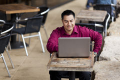 Hispanic Businessman - Telecommuting Internet Cafe. Stock photo of a well dressed Hispanic businessman looking down at a laptop while telecommuting from an stock photography