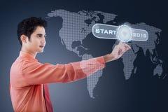 Hispanic businessman touching a start button Stock Images