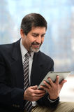 Hispanic Businessman Using Elecroni Tablet Stock Image
