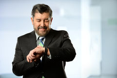 Hispanic Businessman Using Smart Watch. Portrait of Hispanic businessman using smart watch inside office building Royalty Free Stock Photos