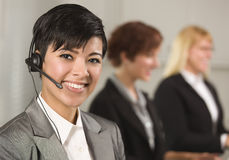 Hispanic Businesswoman with Colleagues Behind Stock Photo