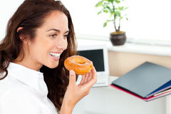 Hispanic businesswoman eating a doughnut in office Royalty Free Stock Image