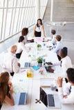 Hispanic Businesswoman Leading Meeting At Boardroom Table Stock Image