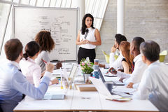 Hispanic Businesswoman Leading Meeting At Boardroom Table Stock Photo
