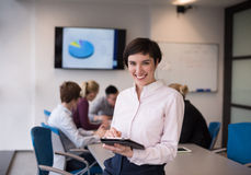 Hispanic businesswoman with tablet at meeting room Stock Photos