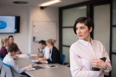 Hispanic businesswoman with tablet at meeting room Stock Photo