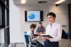 Hispanic businesswoman with tablet at meeting room Royalty Free Stock Photos