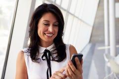 Hispanic Businesswoman Using Mobile Phone In Modern Office Royalty Free Stock Photo