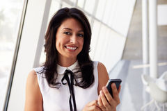 Hispanic Businesswoman Using Mobile Phone In Modern Office Stock Photography