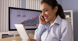 Hispanic businesswoman working at desk Stock Image