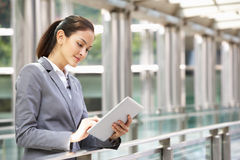 Hispanic Businesswoman Working On Tablet Computer