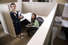 Hispanic businesswomen in cubicle. Two hispanic businesswomen meeting in cubicle working with blueprint Royalty Free Stock Photo