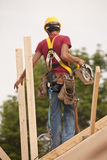 Hispanic carpenter holding circular saw on roof Stock Image