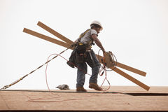 Hispanic carpenter holding circular saw and studs on roof Stock Photos