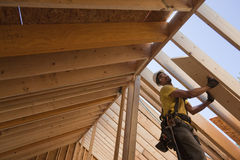 Hispanic carpenter lifting roofing panels onto roof