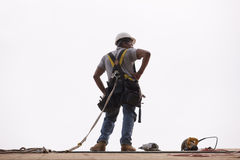 Hispanic carpenter standing on roof with his tools Royalty Free Stock Images