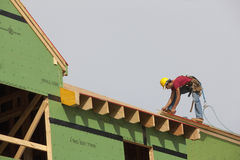 Hispanic carpenter using circular saw on roof Stock Photo